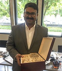 Arghya Bhowmik at his PhD defence, holding a gift from his colleagues: An engraved whiskey bottle with his name